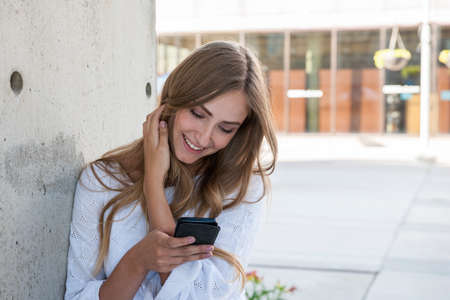 Photo for Young female university student on college campus using her smartphone and smiling standing outside near wall with copy space - Royalty Free Image