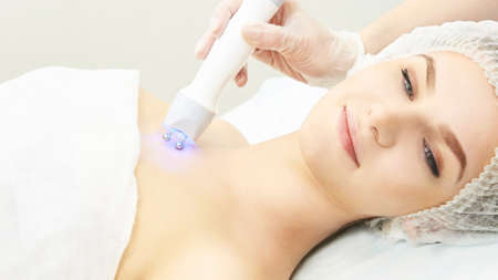 Photo pour Light infrared therapy. Cosmetology head procedure. Beauty woman face. Cosmetic salon device. Facial skin rejuvenation. - image libre de droit