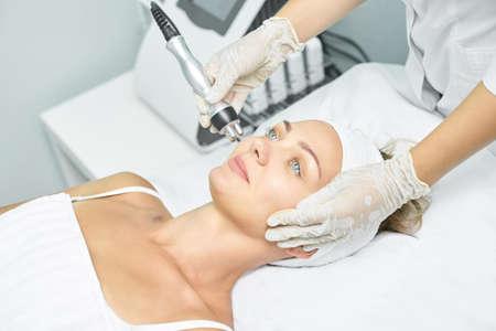 Foto de Dermatology skin care facial therapy. Medical spa anto wrinkles procedure. Woman face rejuvenation. Pretty girl. Rf cosmetician equipment. - Imagen libre de derechos