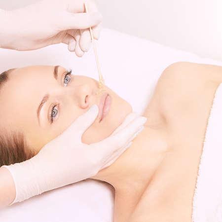 Photo pour Girl wax lip at depilation center. Prfessional remove unwante hair on woman face. - image libre de droit