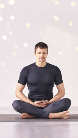 Man sitting at lotus yoga pose. Home morning routine. Teacher fitness studio. Asana class. Online exercise. Relaxation indoor. Male prayer in house room. Light background. Vertical. Close eyes