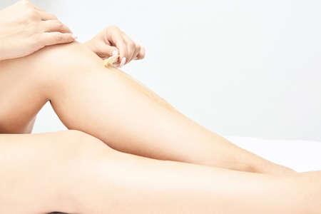 Photo pour Hot hair removal depilation. Female skin routine. Sugar bodycare. Wax correction. Home leg care routine. Light background. Sugaring cosmetics. Girl self treatment. - image libre de droit