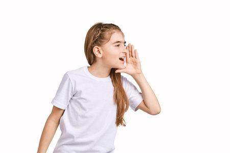 Photo pour Children portrait in white t-shirt. Studio isolated concept. Shout rumor. Secret gossip. Modern communication. Girl hold hand near head - image libre de droit