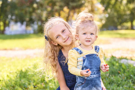 Foto für Two little sisters together at park. Family happiness portrait. Female child relationship. Vacation nature friendship. Happy blond. Curly hair. Green color outdoors - Lizenzfreies Bild