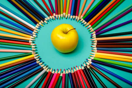 Photo pour Apple and colored pencils are laid out in a circle on blue background. Back to school. Office background. Top view, layout, flatly - image libre de droit