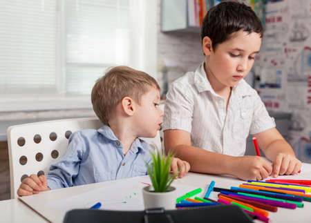 Foto de The child learns at home. Happy children draw in the classroom. Home schooling. Brothers drawing pictures at kindergarten. Boys going to be a painter, artist, talent concept. Creative little boys - Imagen libre de derechos