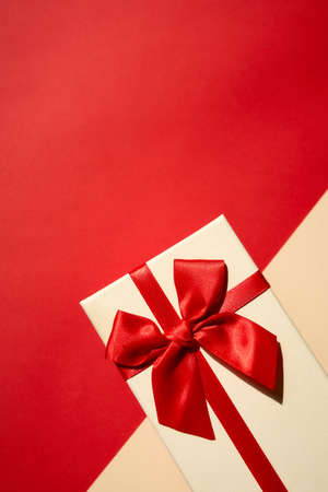 Photo pour White present with red ribbon on the bright red background. Festive backdrop for holidays: Birthday, Valentines day, Christmas, New Year. - image libre de droit