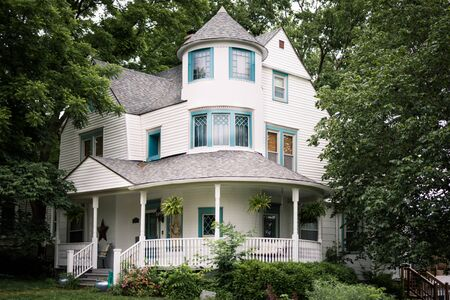 Photo pour Elegant three story home with large wrap around porch surrounded by large trees - image libre de droit