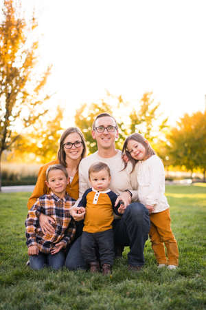 Photo for Young family of five take portraits at fall colored park - Royalty Free Image
