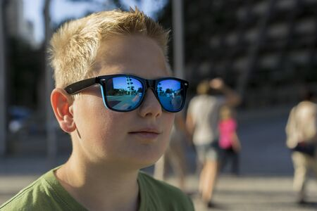 Young blond boy with a serious expression standing outdoors wearing trendy sunglasses reflecting the surrounding urban scene