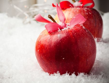 Red delicious Christmas apples resting in snow
