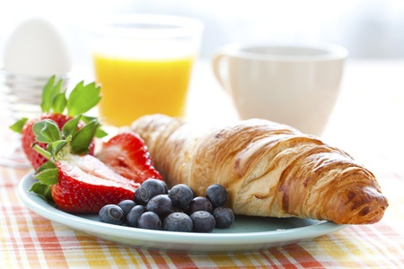Croissant, fresh strawberries and blueberries, coffee, orange juice and an egg for healthy breakfast