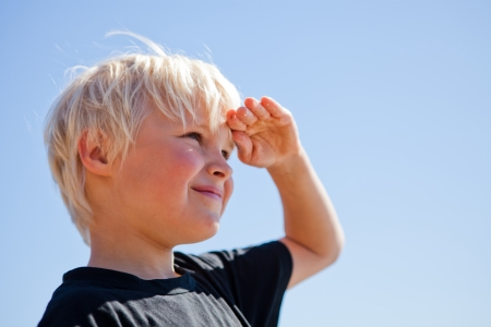 Photo pour Boy outdoors looking ahead with hand on forehead - image libre de droit