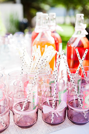 Closeup of decorative pink colored party glasses with straws on table outdoors with bottle of fruit juice in background