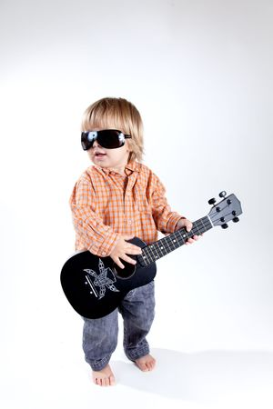 Funny little boy with ukulele guitar, studio shot