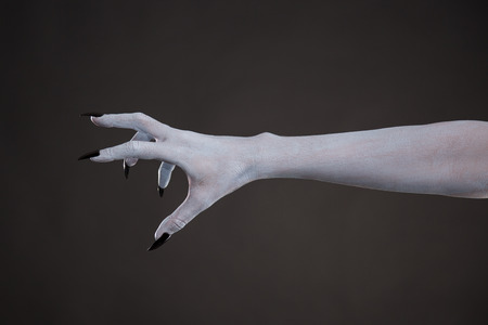 Scary pale skin hand with black nails, body art for Halloween
