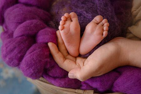 Foto de newborn baby feet and hands of parents. Palms together. - Imagen libre de derechos