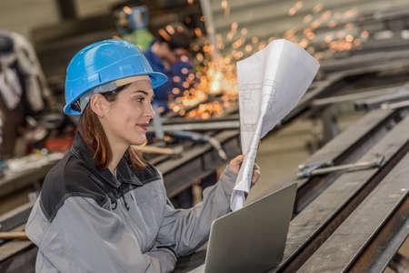Photo pour Happy female worker reads a blueprint in metal factory - image libre de droit