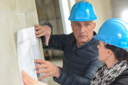 Photo pour Architect and his assistant are checking a blue-print leaning on the wall - image libre de droit