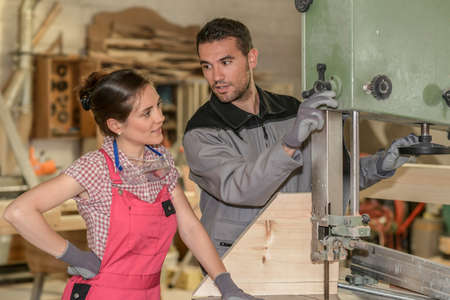 Photo pour Female trainee and male mentor cutting a piece of wood in workshop - image libre de droit