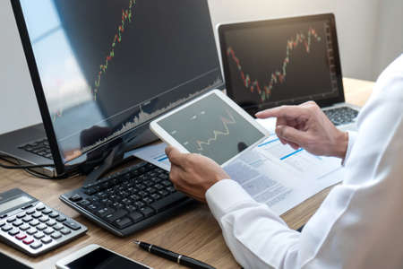 Foto de Stock exchange market concept, stock broker looking at graph working and analyzing with display screen, pointing on the data presented and deal on a exchange, Businessman trading stocks online. - Imagen libre de derechos