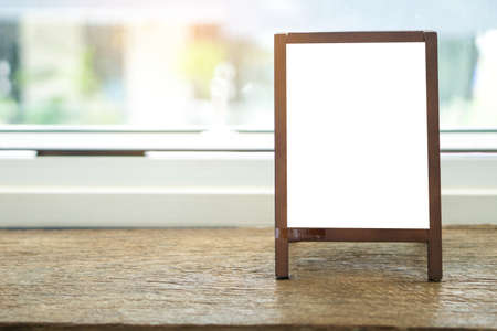 Photo pour Mock up blank advertising whiteboard with easel standing on wood table in cafe and bar restaurant for display or montage of design space for text. - image libre de droit