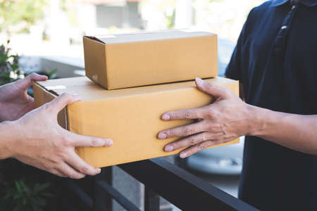 Foto de Delivery mail man giving parcel box to recipient, Young owner accepting of cardboard boxes package from post shipment, Home courier and delivery service mind concept. - Imagen libre de derechos
