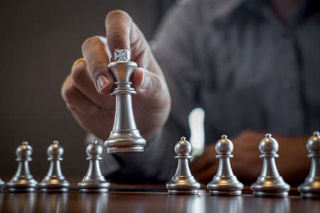 Photo pour Gold and silver chess with player, Intelligent businessman playing chess game competition to planning business strategic to development for win and success. - image libre de droit