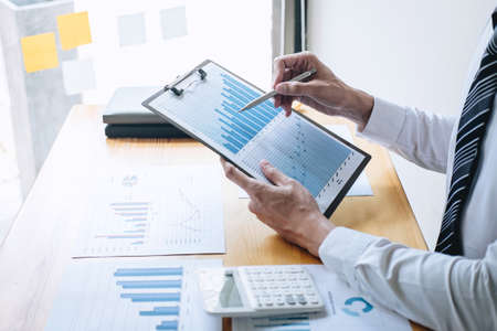 Photo pour Businessman accountant working analyzing and calculating expense financial annual financial report balance sheet statement and analyze document graph and diagram, doing finance making notes on report. - image libre de droit