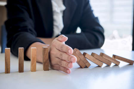 Photo pour Risk and Strategy in Business, Image of hand stopping falling collapse wooden block dominoes effect from continuous toppled block, prevention and development to stability. - image libre de droit