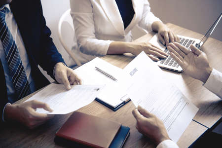 Photo pour Employer or committee holding reading a resume with talking during about his profile of candidate, employer in suit is conducting a job interview, manager resource employment and recruitment concept. - image libre de droit