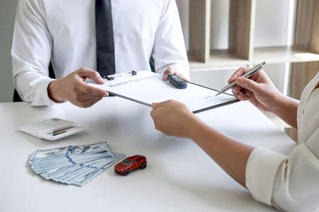 Photo pour Car rent agent manager holding key of new car giving to woman client after signing good deal agreement contract, renting considering vehicle. - image libre de droit