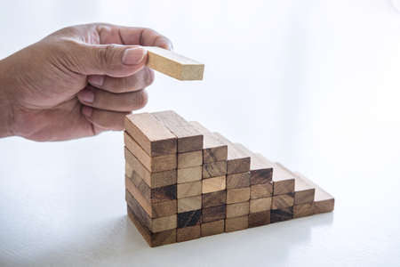 Photo pour Alternative Risk and Strategy in business to make growth, Image of Business man's hand placing making a wooden block stacking hierarchy on growing to lay the foundation and development to successful. - image libre de droit
