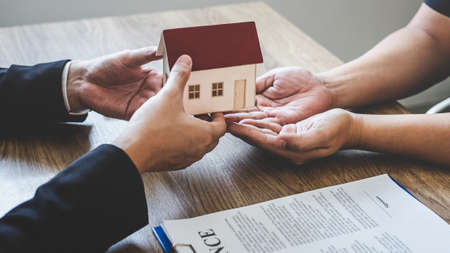 Photo pour Estate agent giving house and keys to client after signing agreement contract real estate with approved mortgage application form, concerning mortgage loan offer for and house insurance. - image libre de droit