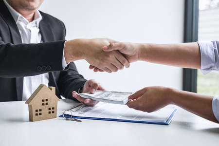 Photo pour Image of successful deal of real estate, Broker and client shaking hands after signing contract approved application form, concerning mortgage loan offer for and house insurance. - image libre de droit