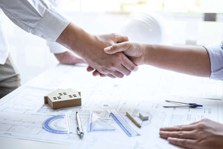 Photo pour Handshake of collaboration, Construction engineering or architect discuss a blueprint and building model while checking information on sketching, meeting for architectural project of partner. - image libre de droit