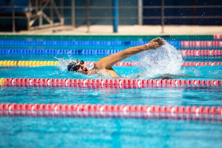 Photo pour Triathlon fitness athlete training swimming front crawl style in the swimming pool with clear blue water. - image libre de droit