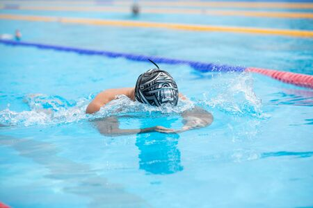 Foto per Athletic man swimming in Breaststroke style in the swimming pool with clear blue water. Triathlon fitness athlete training swimming. - Immagine Royalty Free
