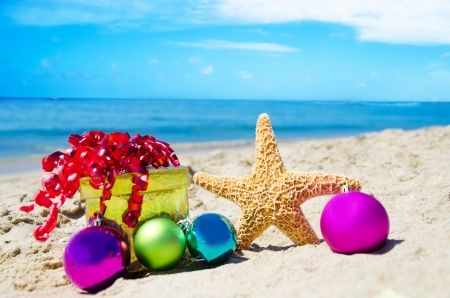Photo pour Starfish with gift box and christmas balls on the beach by the ocean - holiday concept - image libre de droit
