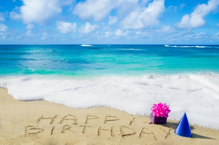 Sign Happy Birthday with decoration on the sandy beach by the ocean