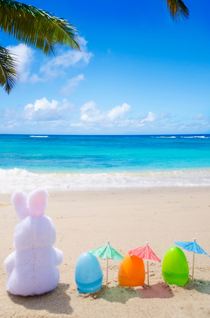 Photo pour Easter bunny and color eggs with cocktail umbrella on the sandy beach by the ocean - image libre de droit
