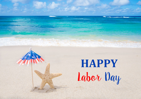 Labor Day USA background with starfishes and decorations on the sandy beach