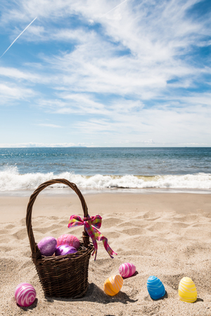 Photo for Easter basket with color eggs on the sandy beach near ocean - Royalty Free Image