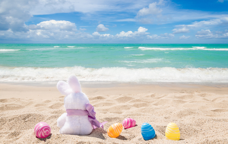 Photo for Easter bunny with color eggs on the sandy beach near ocean - Royalty Free Image
