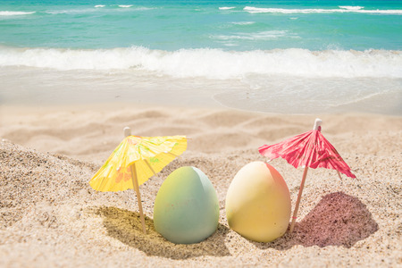 Photo for Happy easter background with eggs and coctail umbrellas on the sandy beach near ocean. - Royalty Free Image