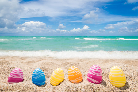 Photo for Happy easter background with eggs on the sandy beach near ocean. - Royalty Free Image