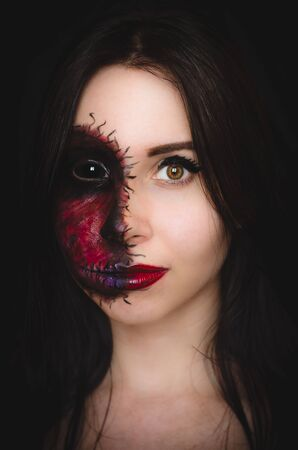 Photo pour Scary portrait of a woman with black eye and a cursed mark on her face on dark background. Demonic nature in an innocent body - image libre de droit