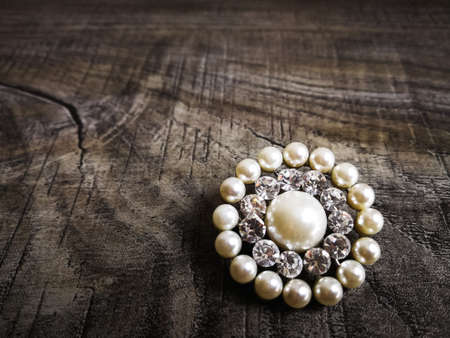 Foto für Brooch with white pearl for clothes isolated on wooden background. Brooch with diamond stone. Old precious brooch - Lizenzfreies Bild