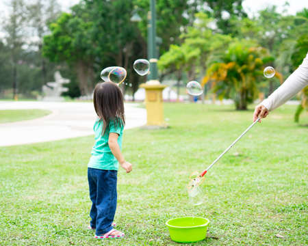 Photo pour Lovely active little asian girl playing with soap bubble outdoor in the park - image libre de droit