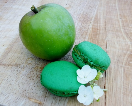 Two bright green apple french macaroons with an apple and flower on a rustic wooden board